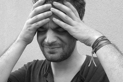 Mann mit Kopfschmerzen hält sich Hände an den Kopf